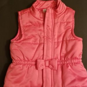 Pink vest with bow.